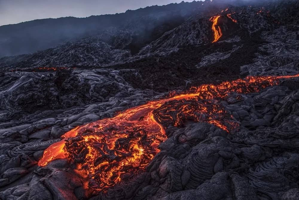 Pahoehoe lava as it flows out of a volcano.