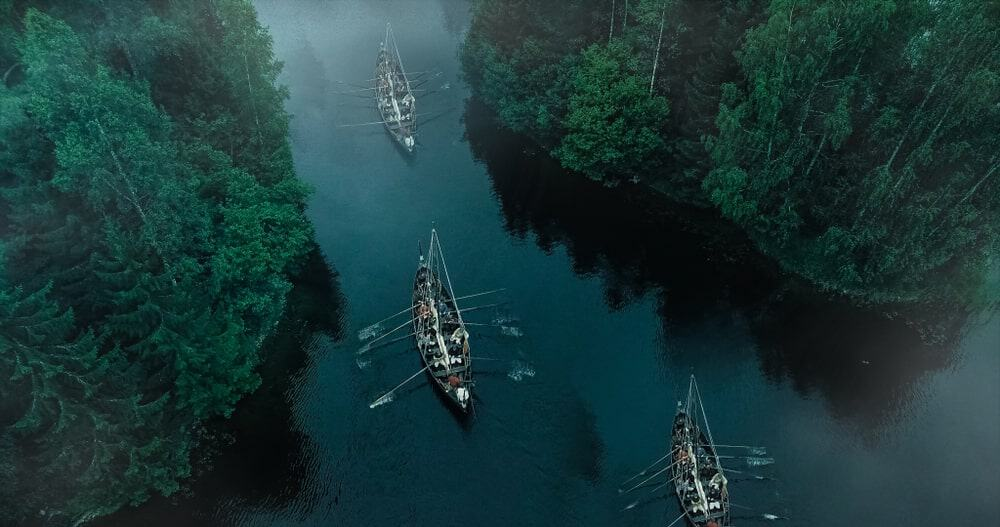 Aerial view of a periodic river with Viking boats sailing across.