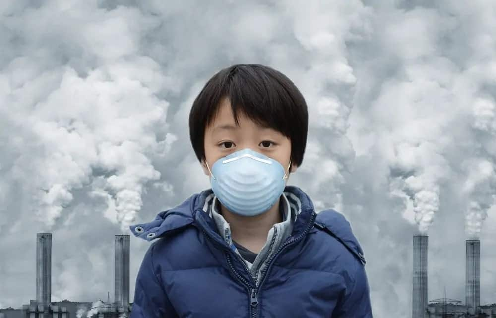 A boy wearing a mask with greenhouse gases on the background.