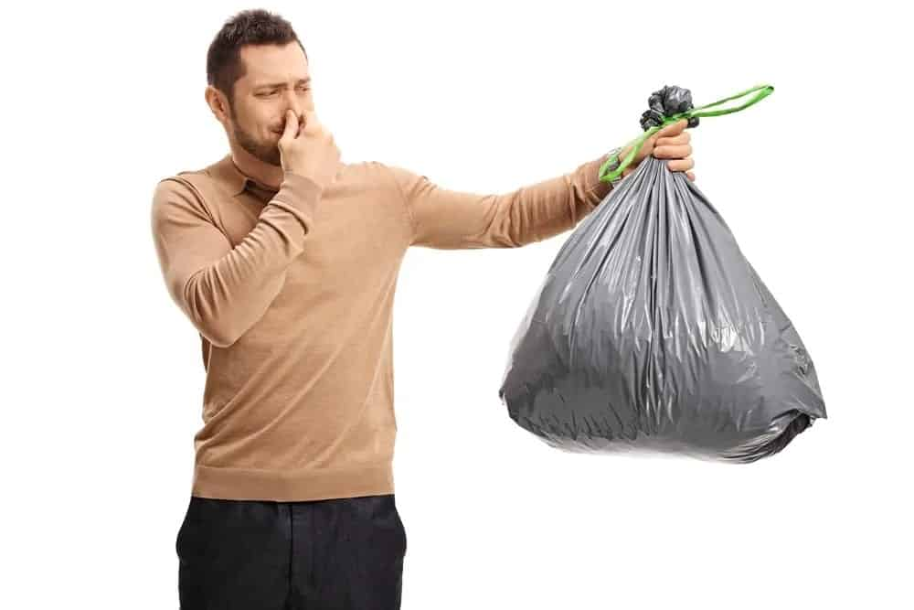 A man holding a garbage bag that emits an unpleasant odor.