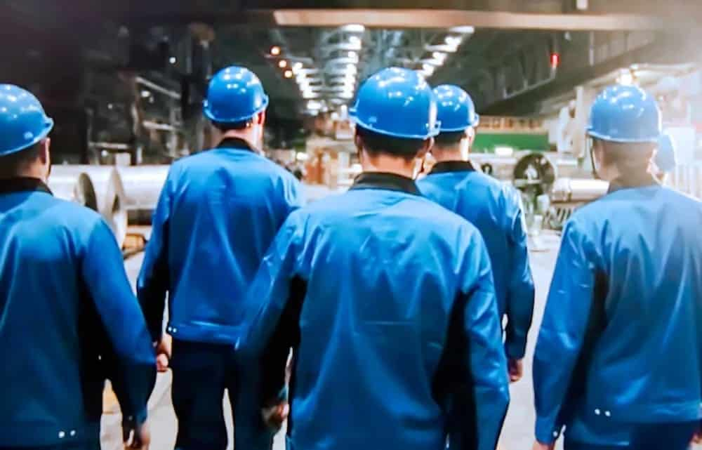Factory workers of a fossil fuel power plant in blue uniforms.