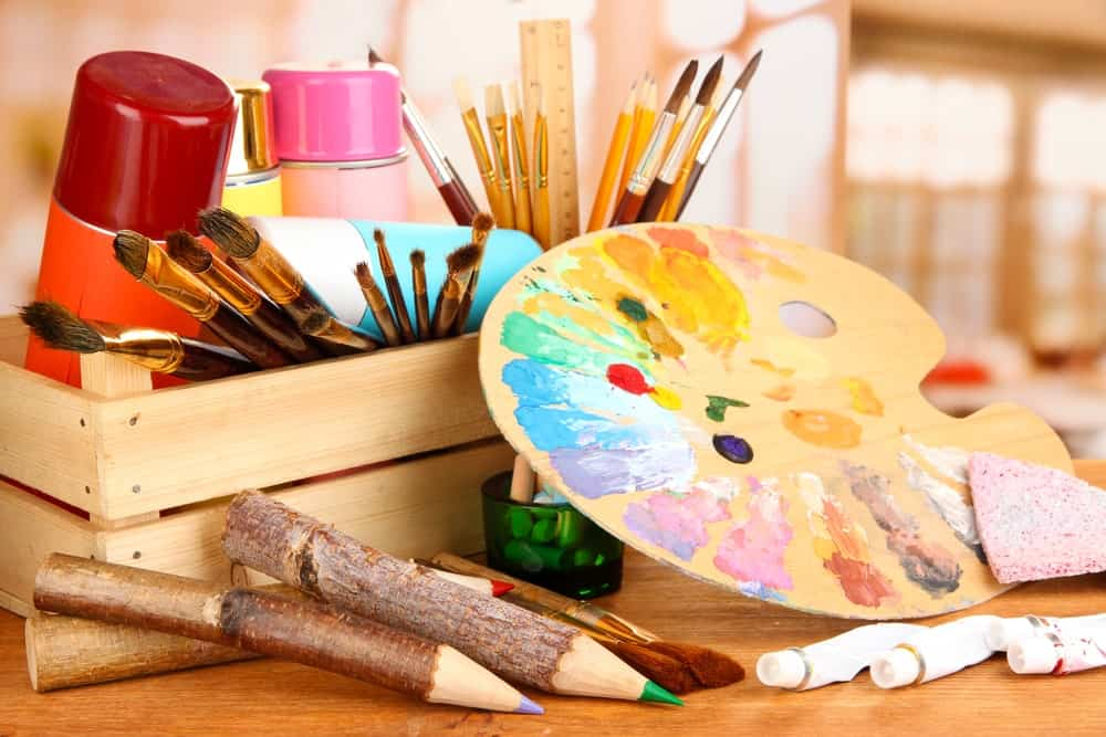 Artistic equipment such as paint, brushes and art palette on a wooden table.