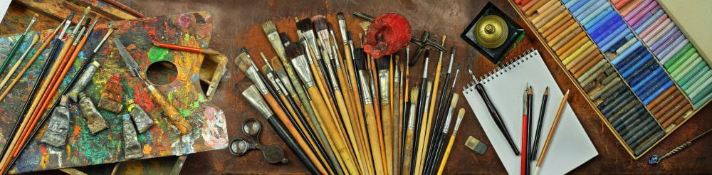 Art tools panorama including sketchbook, brushes, paints, palette, and pastels.