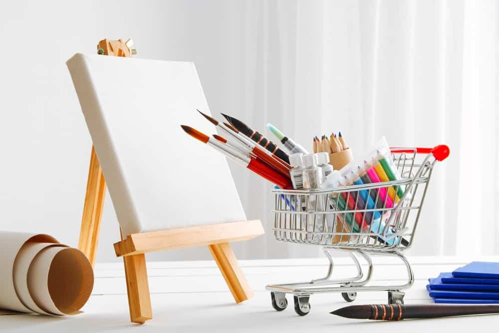 Art canvas along with a mini shopping cart filled with art tools.