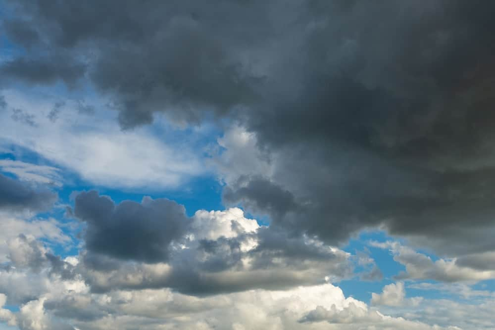 A sky with big fluffy cumulus clouds along with thick storm clouds.