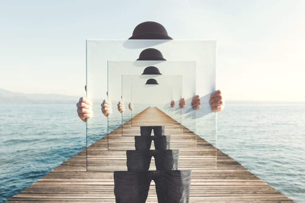 Abstract painting of a person wearing a bowler's hat and holding a square mirror with the sky and sea in the background.