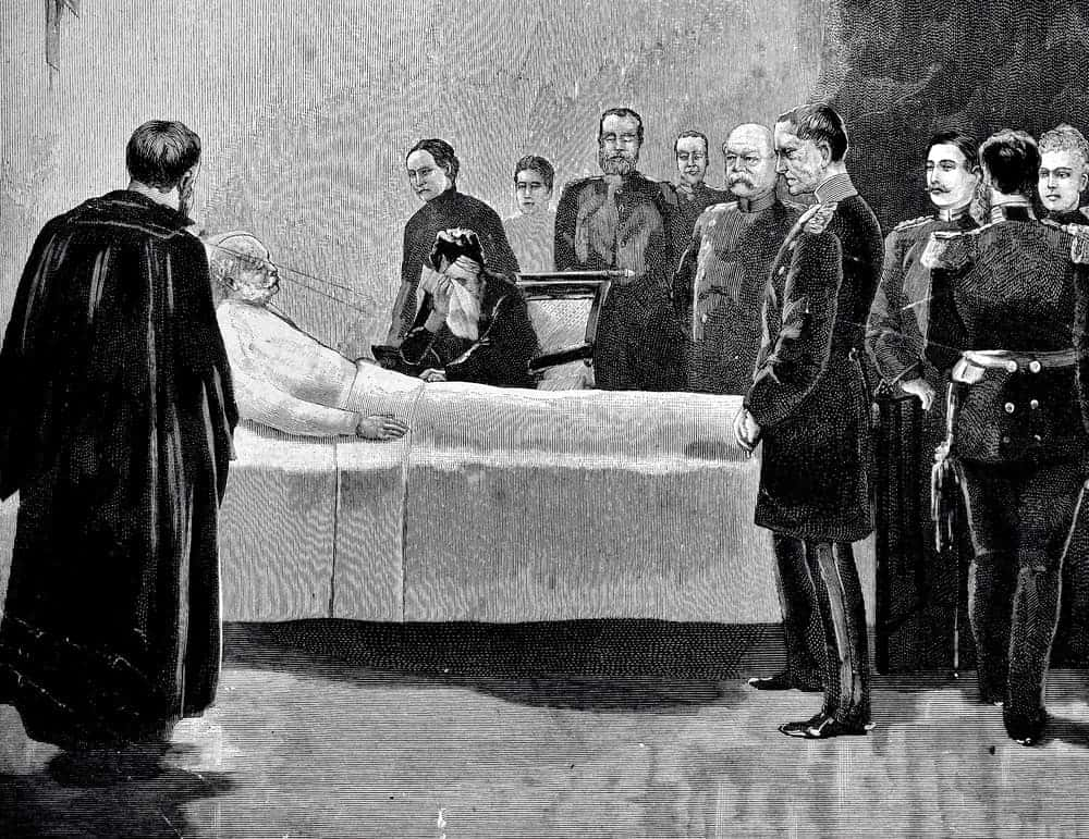 Black and white deathbed scene of an old man lying in bed surrounded by men in different uniforms.