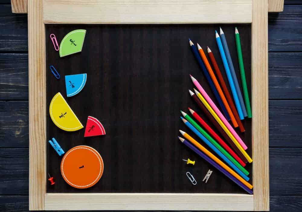 Fractions in colorful visuals with pens and pins on a black board.