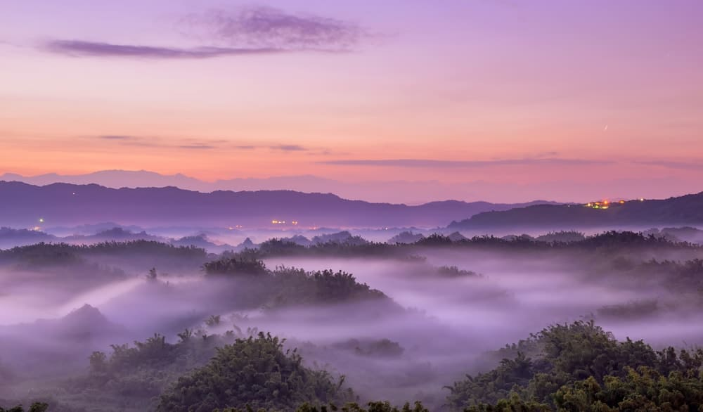 An aerial view of a foggy landscape just before sunrise.
