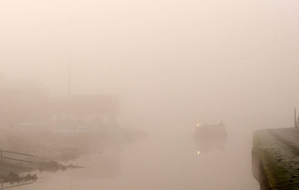 This is a view of a canal with very thick fog.